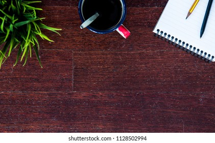 Top view of office wooden tabletop with green plant, enamel cup of coffee and bloc notes with pencil and pen. Copy space for product or texy. Business concept.