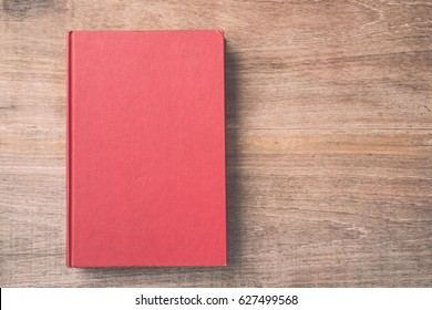Top view old book on wooden plank background.