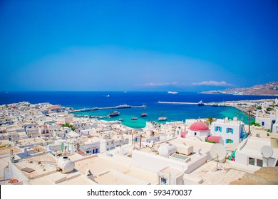 Top view of the old city and the sea on the island of Mykonos, Greece. A lot of white houses against the blue sky