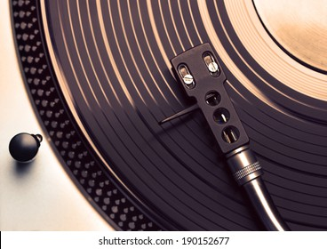 Top view of old fashioned turntable playing a track from black vinyl