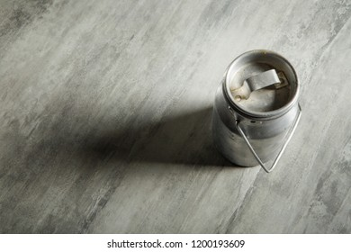 top view of old kind of aluminum bidon with wooden handle for milk storage on gray background