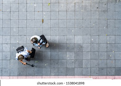 top view of old people walk on pedestrian concrete grey block street  pavement.