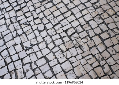 Top view of an old stone paved street.Cobblestone road pavement texture.White tone stone walkway abstract background.Stone texture background.