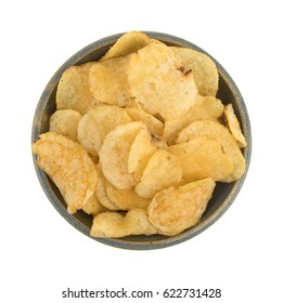 Top view of an old stoneware bowl filled with salt and vinegar flavored potato chips isolated on a white background.