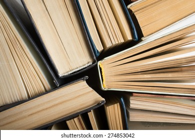 Top view of old used hardback books. Open book, fanned pages. Back to school. Reading are essential for self improvement, gaining knowledge and success in our careers, business and personal lives.