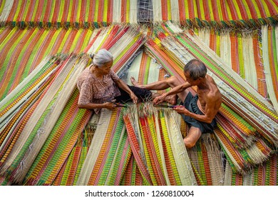 Top view of old Vietnamese lover craftsman making the traditional vietnam mats with happiness action in the old traditional village at dinh yen, dong thap, vietnam, tradition artist concept