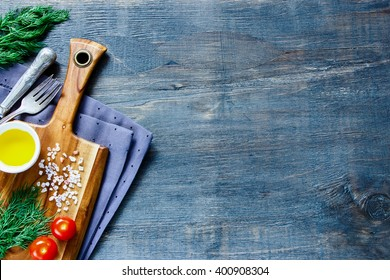 Top view of old wooden kitchen table with cutting board and ingredients on vintage background, place for text.