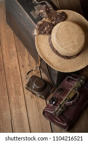 Top view of old wooden suitcase, women's wicker hat, retro camera and travel bag on a dark grunge background. The concept of travel.
