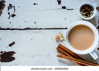 Top view of old wooden table with traditional Indian masala tea in white ceramic cup and spices (cinnamon, anise, cardamom, sugar) over rustic background, copy space.