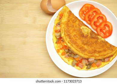 Top view of Omelette (Omelet, Scrambled egg) with ham, tomato, onion, carrot, Champignon Mushroom and grate cheese. Fresh ingredient. Good for breakfast. Still life food. Free space for text.