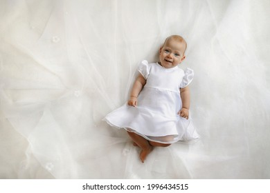 Top view on the adorable female baby lying on the bed. Concept of baby products.