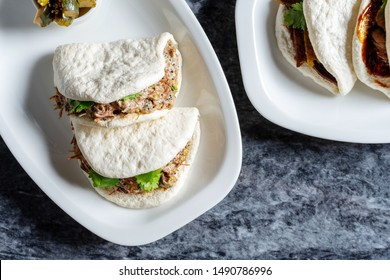 Top view on bao with beef cheek. Gua bao, steamed buns served on white plate. Taiwan's traditional food Gua Bao on marble table. Asian sandwich steamed. Asian fast food