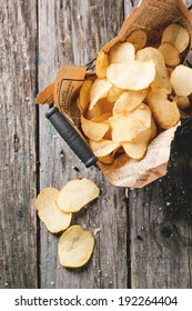 Top view on basket with potato chips with sea salt over old wooden table. See series