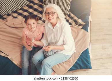 Top view on a beaming senior woman and her granddaughter posing for the camera with cheerful smiles on their faces and a ball of knitting wool in their hands.