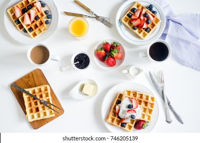 Top view on Belgian waffles with berries and coffee on the white table