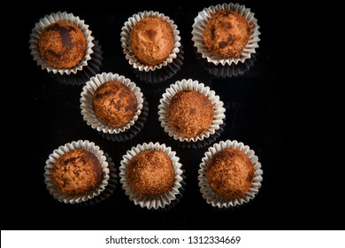 top view on big group of healthy useful organic handmade round chocolate candies decorated with brown cocao powder on black mirror background