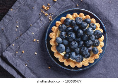 Top view on blueberry tart served on blue ceramic plate over textile napkin.