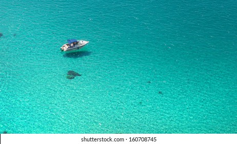 Top view on boat in azure clear water