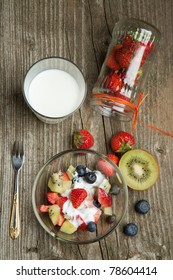 Top view on bowl of fruit salad with fresh strawberries, blueberries and kiwi with glass of milk on old wooden table table