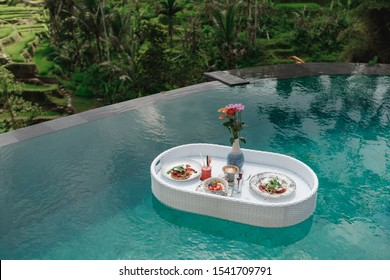 Top view on Breakfast tray in swimming pool, floating breakfast in luxury hotel in infinity pool with view on rice terraces, Ubud, Bali, Indonesia