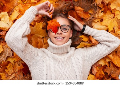 Top view on a cheerful young woman in stylish glasses in a knitted white sweater with an orange sheet near the face in the park on a background of golden foliage. Cute happy girl lies in the forest.