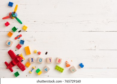 Top view on children toy plane, colorful plastic bricks and wooden cubes on white wooden background.