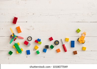 Top view on children toys, colorful plastic bricks and cubes on white wooden background.