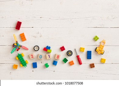 Top view on children toys, colorful plastic bricks and wooden cubes with figures 2018 on white wooden background.