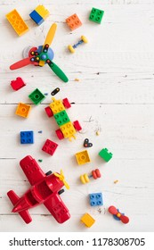 Top view on children toys and colorful plastic bricks on white wooden table. Early learning and development.