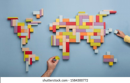 Top view on child's and father's hands playing with colourful wooden bricks building world global map. World unity, diversity and education concept.