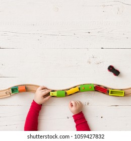 Top view on child's hands playing with colorful  wooden train and railway.