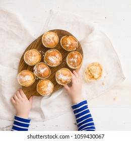 Top view on child's hands holding wooden board with freshly baked home muffins on white table background.