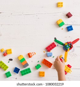 Top view on child's hands playing with colorful plastic toy bricks and small details on white wooden table background
