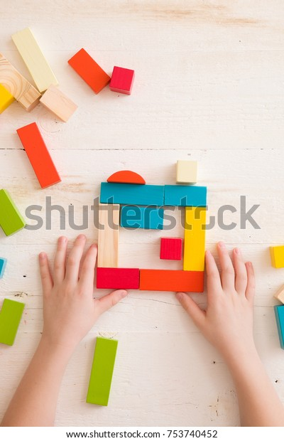 Top view on child's hands playing with colorful wooden bricks on white table background. Boy building with wooden constructor. Education concept