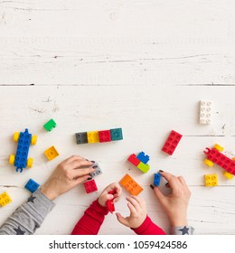 Top view on child's and mother's hands playing with colorful plastic bricks.