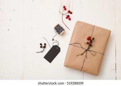 Top view on Christmas gift wrapped in craft and decorateed with various natural things. DIY present idea. Holidays concept.
