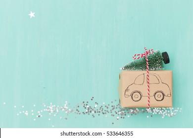 Vue de dessus sur un cadeau de Noël enveloppé dans du papier cadeau d'artisanat décoré de dessin de voiture avec un sapin de Noël sur fond bois turquoise avec des étoiles scintillantes. Nouvel An, fêtes et concept de célébration
