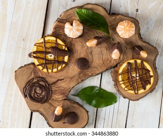 Top view on citruses with chocolate on wooden board