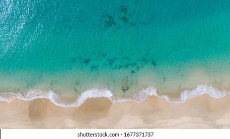 Top View on Coast of Atlantic Ocean, waves on beach aerial view, crystal clear water in Morro Jable Fuerteventura.