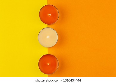 Top view on colored candles with a colorful background