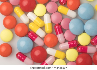 Top view on colored pills on white surface