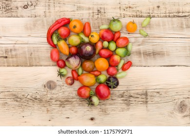 Top view on colorful organic vegetables: tomatoes and paprika in the shape of a heart on old wooden background. Healthy food concept.