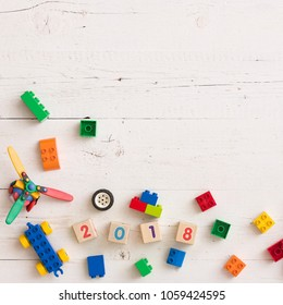 Top view on colorful plastic toy and bricks on white wooden table background. Numbers and toy parts.
