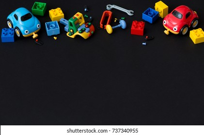 Top view on colorful plastic bricks, cars and details of toys on black paper background. Parts of bright small spare parts for toys.