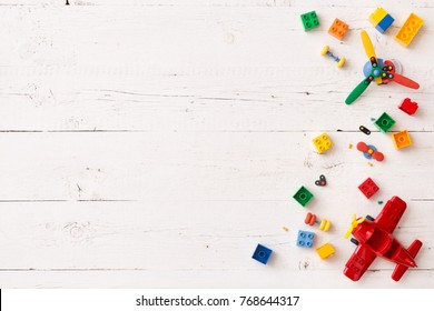 Top view on colorful toy bricks on a white wooden background. Toys in the table