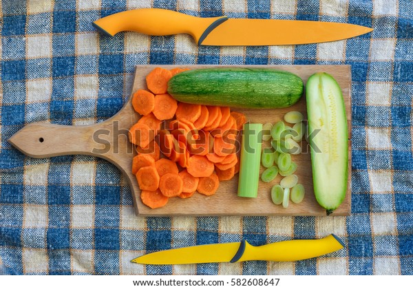 Top View on colorful Vegetables and knives on kitchen board. Food preparation concept.