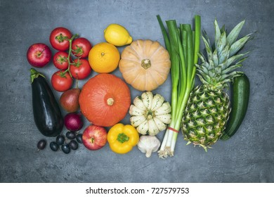 Top view on colourful fresh vegetables arranged around border with empty space for text.