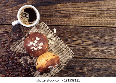 Top view on cup of coffee and tasty chocolate cupcakes on wooden background