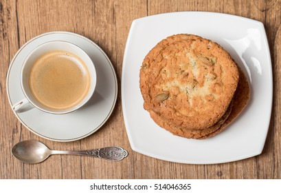 Top view on cup of coffee and plate with cookies on wooden table