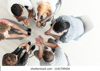 Top view on difficult youth talking to a therapist while sitting in a circle during meeting